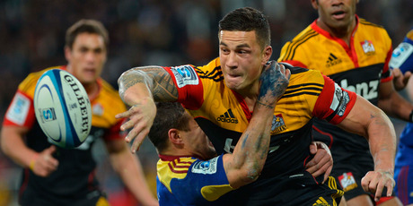 Chiefs second five-eighths Sonny Bill Williams offloads in his trademark style while held by Tamati Ellison in Dunedin last night. Picture / ODT