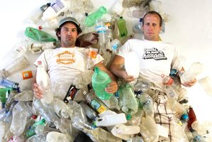 Camden Howitt and Sam Judd lying in less than one-fifth of the plastic bottles picked-up by volunteers in one day, from the shores of uninhabited Rangitoto Island. Photo / Supplied