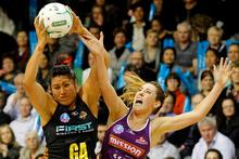 Magic Goal Attack Julianna Naoupu and Firebirds Centre Elissa Macleod fight for the ball. Photo / Christine Cornege