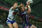 Anthony Quinn of the Storm is challenged for the ball by Sandor Earl of the Raiders during the round 18 NRL match between the Melbourne Storm and the Canberra Raiders. Photo / Getty Images.