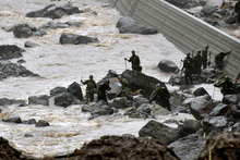 Japan's Self Defense Force members search for missing residents in the rain, in Takeda, Oita Prefecture, Japan. Photo / AP