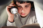 Reading under the cover of darkness may not protect children from bleak tales of lost childhoods found through the portal of their story books. Photo / Thinkstock