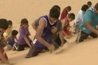 Just before dawn, 100 boxers run up a steep sand dune pursued by the unrelenting voice of their trainer who believes his unusual preparation methods will help India succeed at the Olympics.