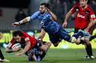 Zac Guildford is lowered in the tackle of Jacques Potgieter of the Bulls. Photo / Getty Images
