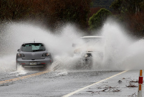Cars throw up curtains of water on flooded State Highway 1 just north of Turangi. Heavy rain fell over the North Island yesterday as the front moved across the country. Photo / Alan Gibson
