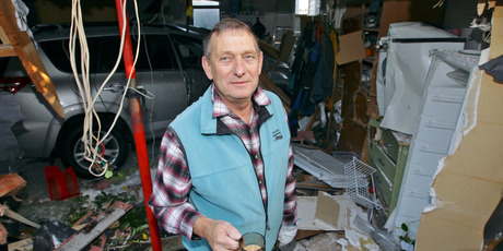 John Pingram surveys the damage to his garage caused by property developer Jonathan King's car crashing into it. Photo / Michael Craig