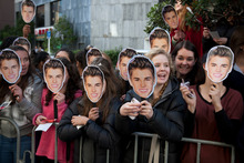 Female fans holding masks of their idol gather outside the Langham Hotel in Auckland hoping to see Canadian pop star Justin Bieber. Pictures / Greg Bowker