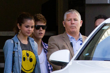 Justin Bieber, with girlfriend, singer Selena Gomez (left), leaves the Langham Hotel from a secret exit avoiding hundreds of young fans today. Photo / Greg Bowker