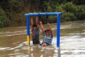 Rapi Kihi,11, (left) and Trent Kaka,10, play on the swing at the Buller Bridge playground reserve. The heavy rain which soaked the West Coast is now heading north. Photo / APN