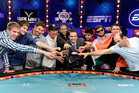 Tournament director Jack Effel, center holding a trophy, poses with the final nine players after the conclusion of the Main Event at the 43rd annual World Series of Poker. Photo / AP.