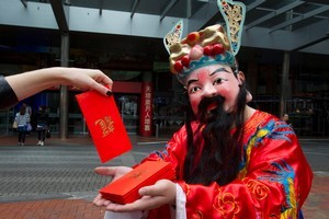 Steve Zhang, dressed as a god of fortune, hands out envelopes of lucky gold chocolate coins in Auckland yesterday. Photo / Brett Phibbs