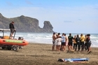 Police and surf lifesavers hold a debriefing at Bethells Beach after searching without success for the 12-year-old believed to have been swept away by a rip while swimming at nearby O'Neill Bay. Photo / Greg Bowker