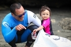 Musician Francis Kora and his daughter Coco help clean up Piha beach. Photo / Sylvie Whinray