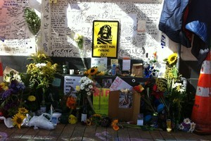 Messages, flowers and empty alcohol bottles adorn the spot where Blanket Man would often sit in central Wellington. Photo / APNZ