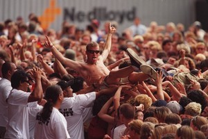 Concert security gives one of the crowd a hand across the barrier from the mosh pit during the 1999 Big Day Out. File photo / Brett Phibbs
