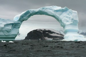 A dramatic arch of ice at Cuverville Island in Antarctica dwarfs the Aleksey Maryshev. Photo / Jim Eagles
