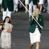 A girl carrying a cauldron walks beside Australia's Lauren Jackson waving her country's national flag during the Opening Ceremony. Photo / AP