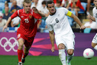 Belarus' Artem Solovei, left, battles for the ball against New Zealand's Ryan Nelsen, right, during the group C men's soccer match. Photo / AP.