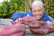 Teina Tangimetua with some of her brother's giant kumara harvest. Photo / Meg Liptrot