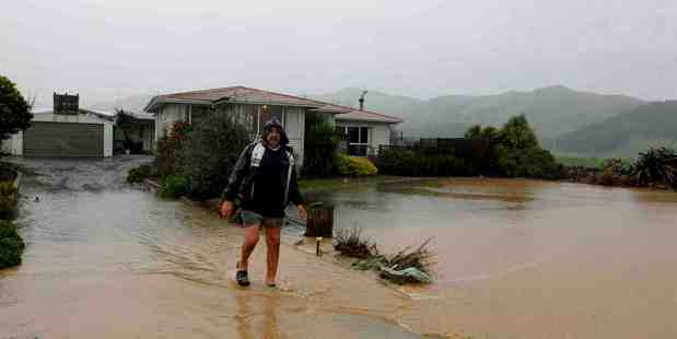 Des Hunt walks down the driveway on his Thorp Rd property outside Paeroa during heavy rains today. Photo / Christine Cornege