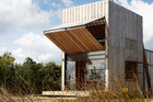 Ken Crosson's 'hut on sleds', a 40sq m bach on the Coromandel Peninsula that can be shifted around its beach-front section. Photo / Supplied