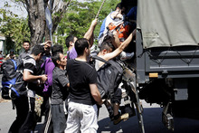 Asylum seekers who were arrested while looking for a way to travel to Australia board a police truck in Sidoarjo, East Java, Indonesia.  Photo / AP