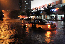 A taxi driver walks away after his car was stranded in a flooded street following a heavy rain in Beijing. Photo / AP