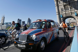 Taxis drive slowly across Tower Bridge in London in protest at not being allowed to use the Olympic lanes. Photo / AP