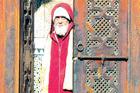 A man in a red jellaba stares out from an intricately carved doorway in Fez. Photo / Guy Needham