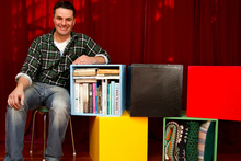 Justin Newcombe and his storage cubes painted in Olympic colours. Photo / Steven McNicholl