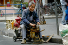 An elderly man sharpens knives on the roadside in Old Shanghai. Photo / Kenny Rodger