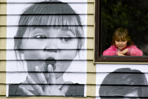 Glen Innes 3-year-old Koalani Patuwai watches her image being put up as part of an international community art project. Picture / Richard Robinson