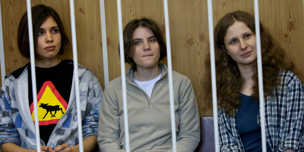 From left, Nadezhda Tolokonnikova, Maria Alekhina, Yekaterina Samutsevich, members of feminist punk group Pussy Riot sit behind bars at a court room in Moscow, Russia. Photo / AP