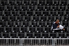 A lone man sits in an empty section of seats inside Earls Court during during a women's volleyball preliminary match between China and Turkey on Monday. Photo / AP