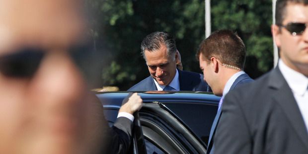 Republican presidential candidate Mitt Romney gets in his vehicle as reporters shout questions at him in Poland. A comment from his aide has capped a horror gaffe week. Photo / AP