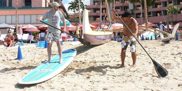 Jim Eagles (left) is taught paddle skills on Waikiki Beach. Photo / Jim Eagles