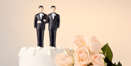 Still life of the top of a wedding cake with two miniature grooms cake topper and roses at the side