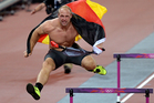 Germany's Robert Harting leaps over hurdles and wears his national flag to celebrate his win in the men's discus throw during the athletics in the Olympic Stadium. Photo / AP.