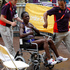 Namibia's Beata Naigambo is moved in a wheelchair after finishing the women's marathon. Photo / Mark Mitchell.