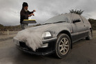 Vic Cassin sweeps ash from one of the vehicles parked on his section south of Turangi, which was in the path of the ash cloud from last night's eruption of Mt Tongariro. Photo / Alan Gibson