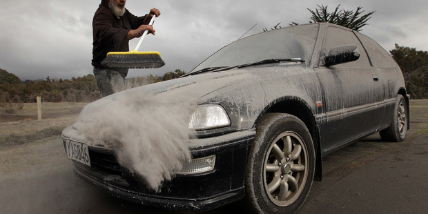 Vic Cassin sweeps ash from one of the vehicles parked on his section near Turangi, which was in the path of the ash cloud that resulted from last nights eruption of Mt Tongariro. Photo / Alan Gibson