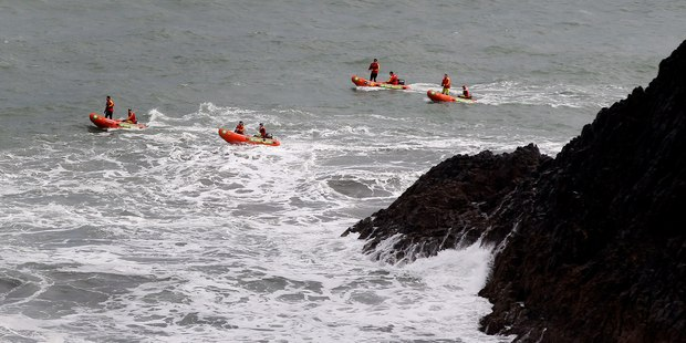 Rescue boats search the seas around Paritutu Rock yesterday for the two students and instructor missing since plunging from the rock into stormy seas on Wednesday. Photo / Christine Cornege