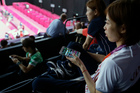 Satoko Suetsuna watches badminton matches with Twitter on her phone at hand. Photo / AP