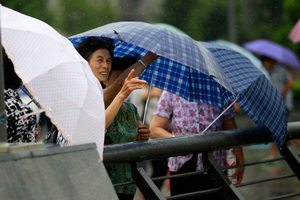 Tourists braved winds last week as typhoon Saola approached the city of Shanghai, China. Photo / AP