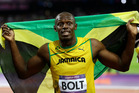 Jamaica's Usain Bolt holds his national flag following his win. Photo / AP.