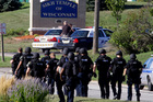 Police walk near the Sikh Temple of Wisconsin in Oak Creek. Photo / AP