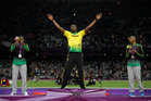 Jamaica's gold medal winner Usain Bolt is flanked by his teammates silver medal winner Yohan Blake, left, and bronze medalist Warren Weir during the ceremony for the men's 200-meter final during the a