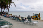 A bulldozer at the Edgewater Resort restores the beach while tourists enjoy the sun. Photo / Jim Eagles