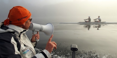 Legendary rowing coach Dick Tonks works the megaphone on a misty morning at Lake Karapiro. Picture / Janna Dixon