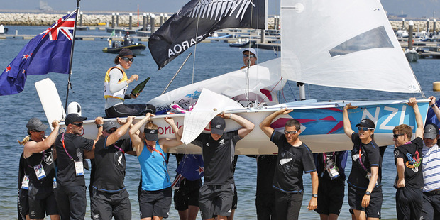 Jo Aleh, left, and Olivia Powrie and their dinghy are carried ashore by members of the New Zealand sailing team after winning gold medal women's 470. Photo / Mark Mitchell
